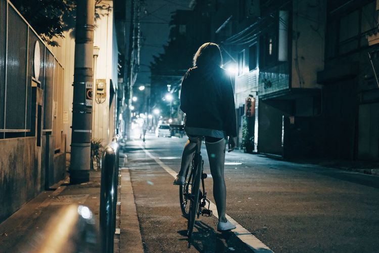 Rear View Of Woman On Bicycle At Night