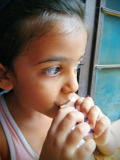 Close-up of girl eating chocolate against window