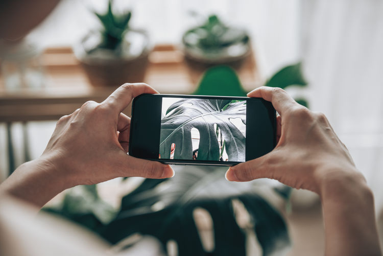 Midsection of man photographing through smart phone