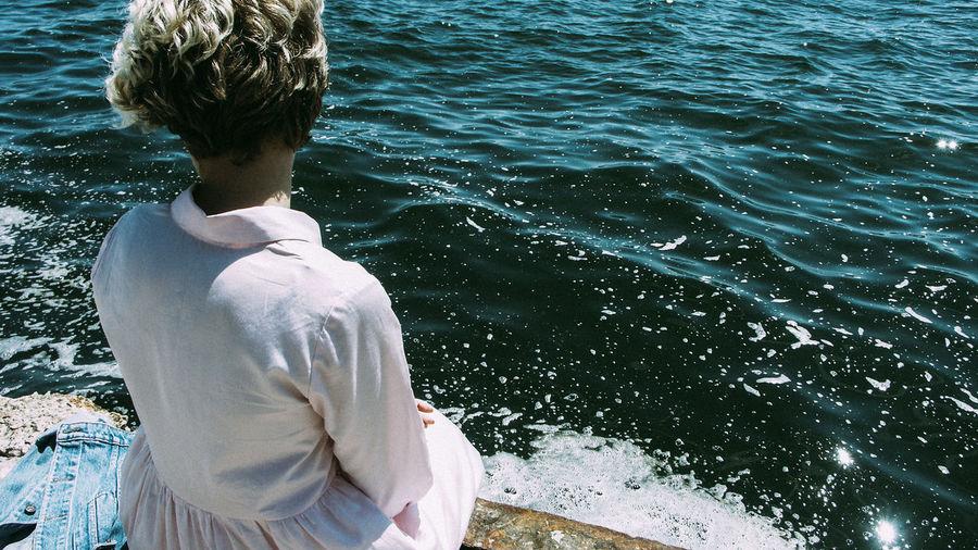 Rear view of teenage girl standing in sea