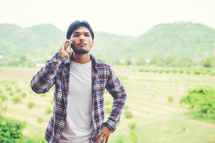 Young Man Using Mobile Phone While Standing On Landscape