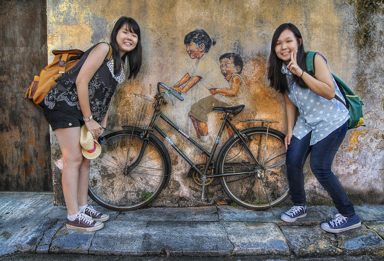 teens and mural Transportation Young Adult Bicycle Young Women Friendship Full Length Casual Clothing Group Of People Togetherness Leisure Activity Women Teenager Child Looking At Camera People Long Hair Smiling Architecture Portrait Hairstyle Adolescence  Outdoors Mural Art Color Wall Picture Teenage Girls Chinese Pose Street Joyful Happy Action Creativity Sightseeing Graffiti Architecture Outdoor Travel, Penang Graphic Lifestyles Contemporary Painting Craft