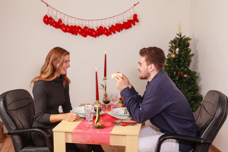 Smiling young couple having food at table