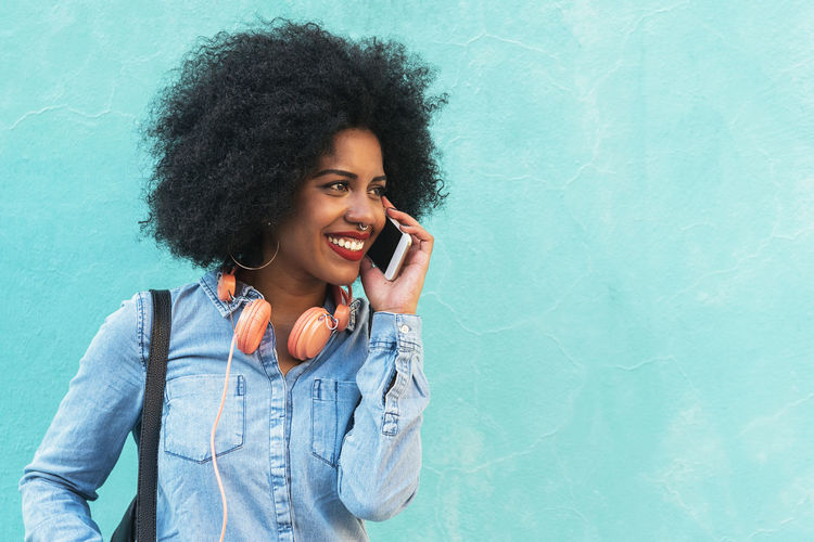 Beautiful afro american woman using mobile in the concept. Adult African Afro American Beautiful City Life Copy Space Hair Headphones Lifestyle Mobile Phone Wall Woman Black Casual Clothing Communication Curly Hair Denim Ethnic Outdoors People Portrait Smart Phone Technology Urban