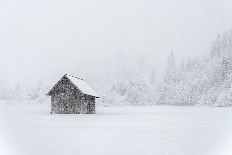 House on snow covered land and trees against sky