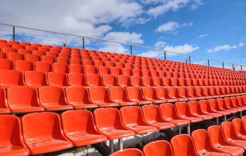 Empty red chairs at stadium against blue sky