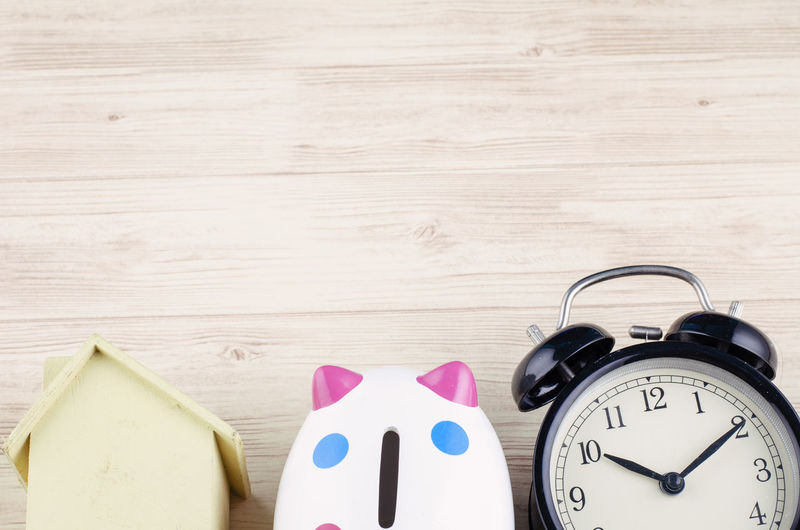 Time for saving money concept, flat lay image of alarm clock, house and piggy bank on wooden desk Clock Time Indoors  Table Still Life Wood - Material Alarm Clock No People Close-up Number High Angle View Copy Space Art And Craft Pink Color Deadline Minute Hand Creativity Group Of Objects Accuracy Wall - Building Feature Clock Face Wood Grain