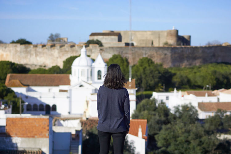 Rear view of woman looking at buildings against sky
