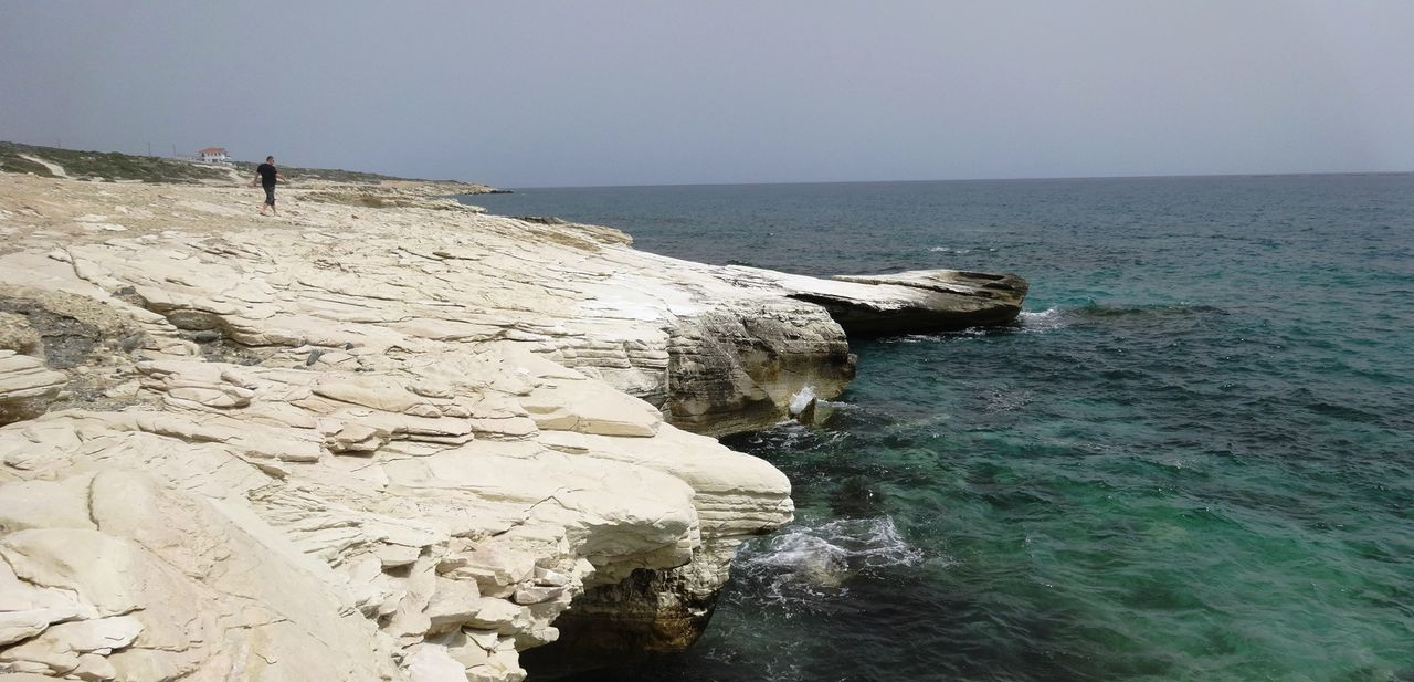 sea, water, rock - object, horizon over water, nature, scenics, beauty in nature, tranquil scene, tranquility, outdoors, clear sky, day, standing, sky, one person, people