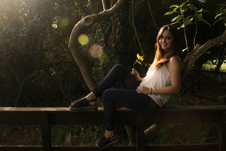Full length of smiling woman sitting on railing by trees