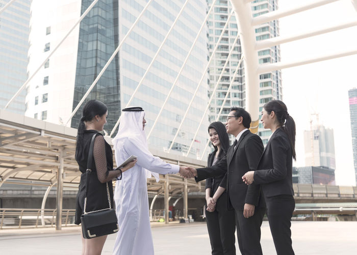 Male colleagues shaking hands while standing with businesswomen