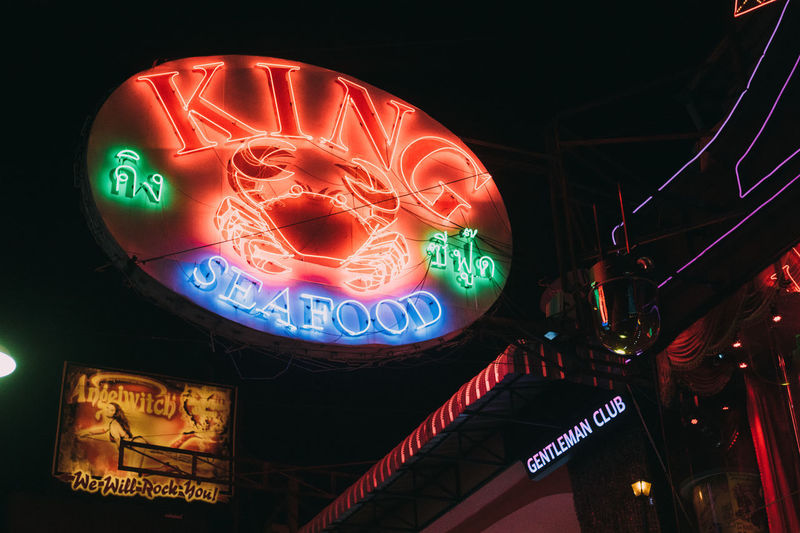 Low angle view of illuminated information sign at restaurant