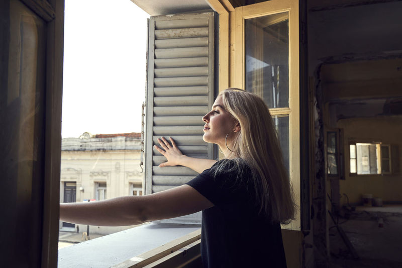 Side view of woman standing against window