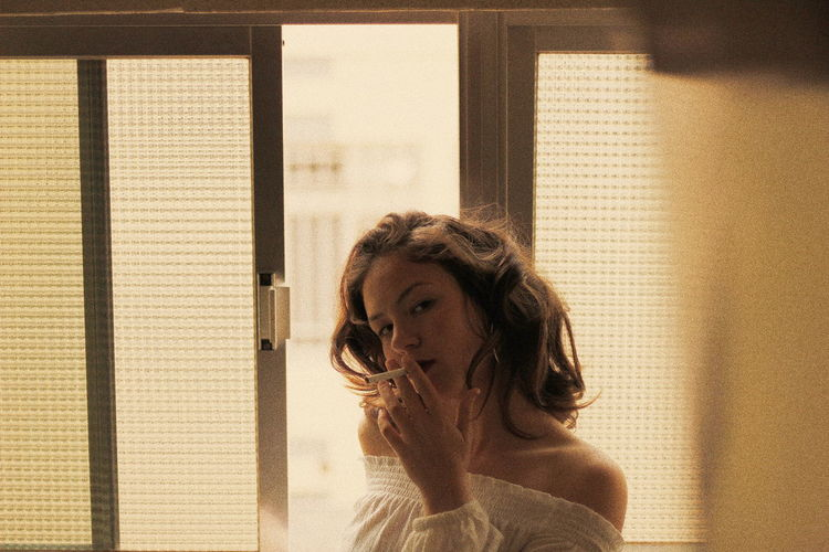 Portrait Of Young Woman Smoking While Standing Against Window At Home