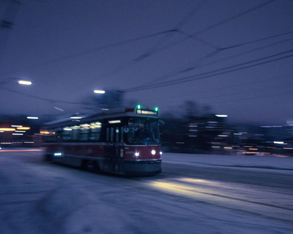 A streetcar passes Riverdale Park on a cold Christmas Eve in Toronto, Ontario. Mobility In Mega Cities Toronto Tram Winter Architecture Blurred Motion Building Exterior Illuminated Land Vehicle Long Exposure Mode Of Transport Motion Night No People Outdoors Panning Sky Streetcar Transportation