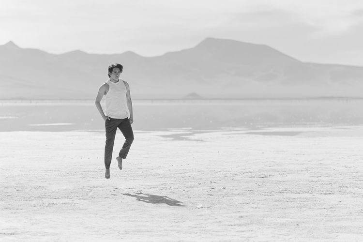 Young Man Levitating Above Salt Flat During Sunny Day