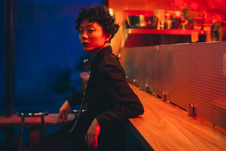 Portrait of woman looking away while sitting in illuminated nightclub