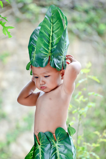 Cute boy wearing leaves and garland standing outdoors