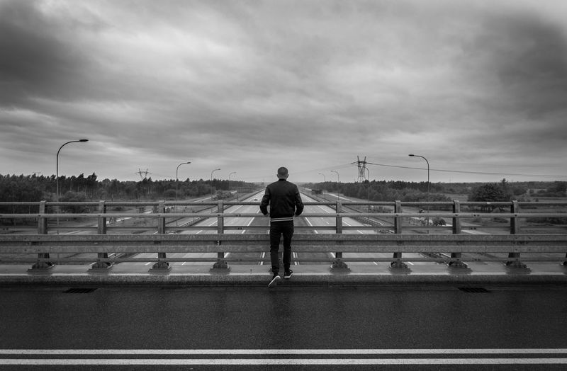 Rear view of man standing on bridge against sky