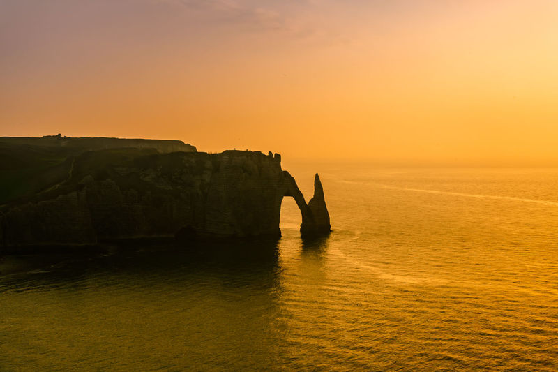 Silhouette rock formation by sea against sky during sunset