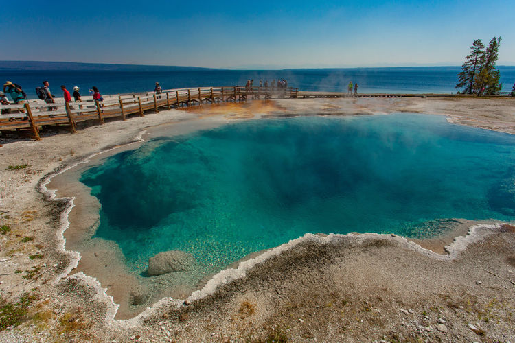 Black Pool Spring. West Thumb Geyser Basin. Yellowstone National Park, USA. Hot Springs National Park Steam Tourists Travel West Thumb Geyser Basin Yellowstone National Park Blue Sky Blue Water Bright Blues Color In Nature Deep Pool Geothermal Feature Hot Spring Incidental People Lake Yellowstone Land Nature Outdoors Power In Nature Public Lands Scenics - Nature Steam Turquoise Colored Water