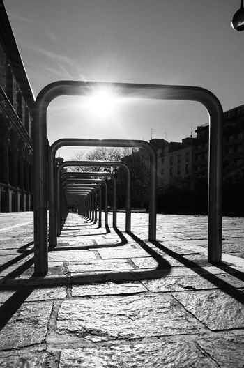 Empty benches on street during sunny day