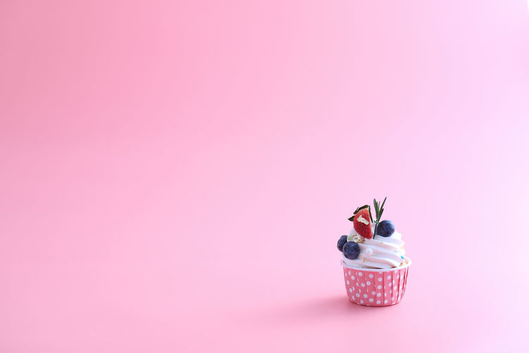 Close-up of cupcakes on pink over white background