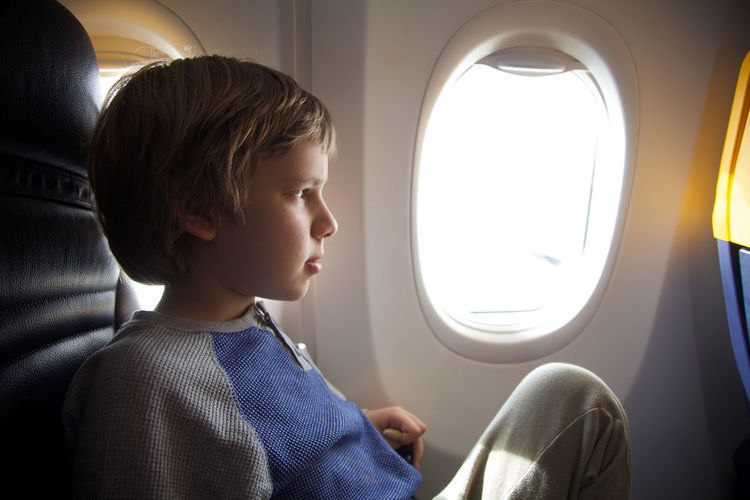 Boy looking through airplane window