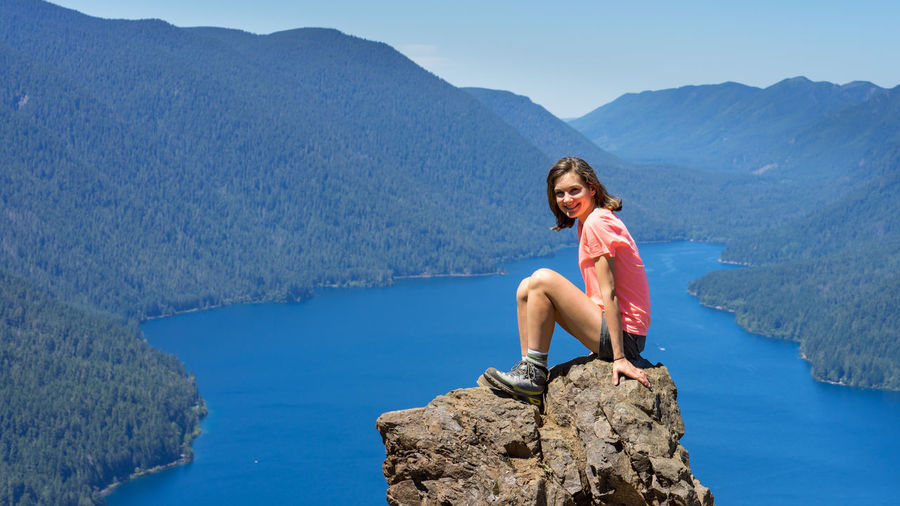 Woman sitting on rock by mountains against sky