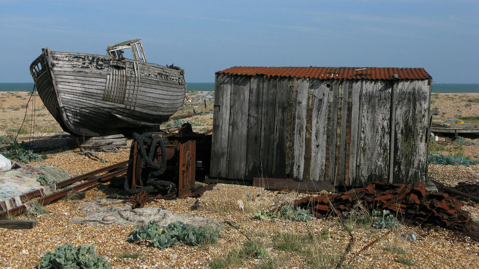 Derelict Fishing Boat and Hut, Dungeness A Wooden Boat: Vessel, Craft, Watercraft, Ship; Boat, Fishing Boat, Sail, Abandoned Architecture Broken Building Exterior Built Structure Damaged Destruction Deterioration Dungeness Photostory Beach Land Landscape Big Sky Skies Clouds Cloud Grasses Flat Barren Beauty Photography Photographer Photograph Images Colour Color Black And White Monochrome Documentary Reportage Taking Photographs Photos Fotos Film Digital Images An Fishing Boat Stranded House Landscape Dungeness Big Sky Skies Houses White Beach Sea Buildings Grass Sand Plants Photography Photographer Photograph Documentary Reportage Taking Photos Fotos Foto Photo Taking Photos Film Digital Image Color Colour Obsolete Old Photography Taking Photos Reportage Documentary Photography Residential Structure Roof Ruined Run-down Wood Wood - Material Wooden