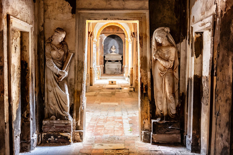 Cemetery corridor background with two statues .