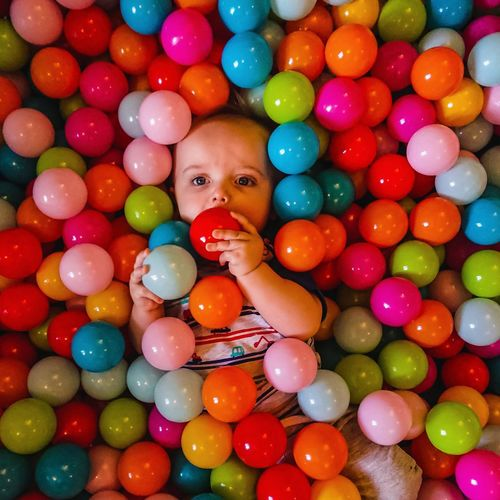 High Angle Portrait Of Baby Boy Playing With Colorful Balls