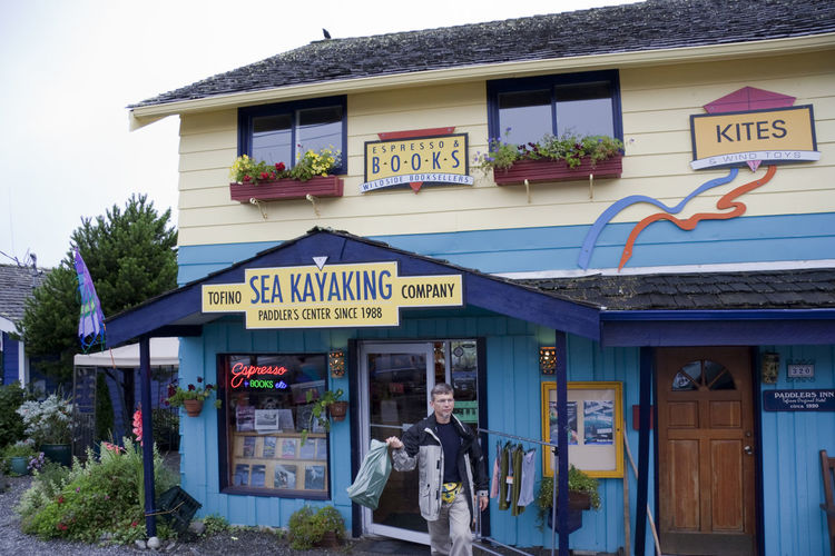 Sports Shop with Customer - Tofino, Vancouver Island, British Columbia, Canada Aquatic Sport Architecture Building Exterior Canada Communication Customer  Façade Front View House Man One Man Only Outdoors People Retail  Sea Kayak Sea Kayaking Shop Sign Small Business Sport Shop Sports Shop Store Text Water Sport Western Script