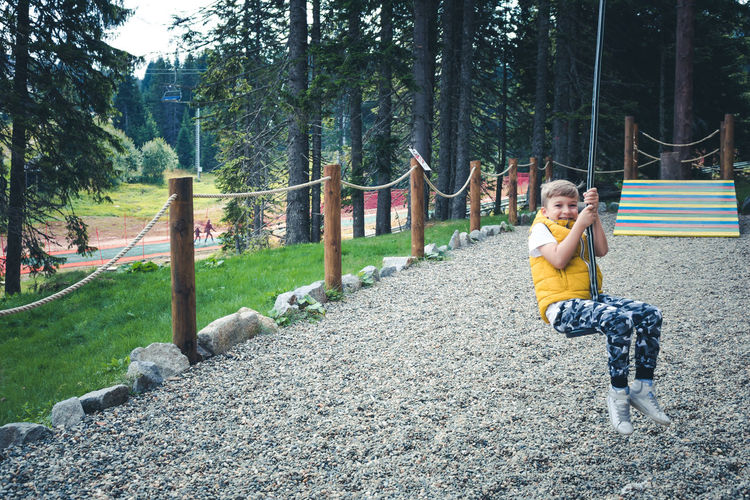 Happy boy on zip line having fun in the park.