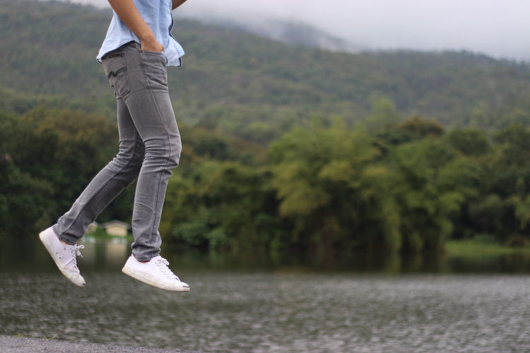 Low Section Of Man Jumping By Lake Against Tree Mountains