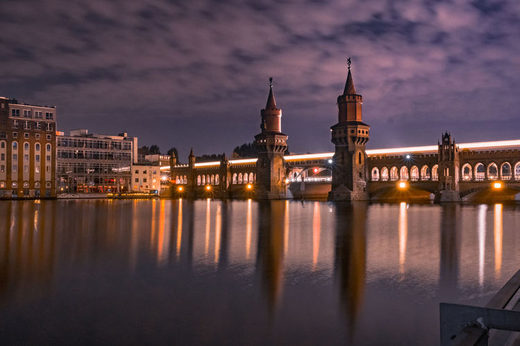 Illuminated oberbaum bridge over spree river against cloudy sky