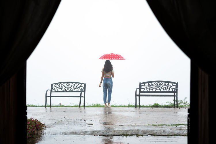Rear view of woman standing on rainy day