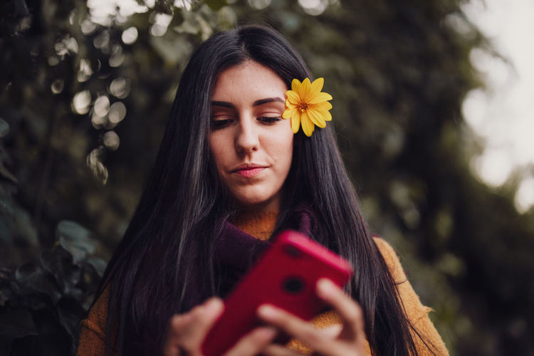 Portrait of beautiful young woman holding red flower