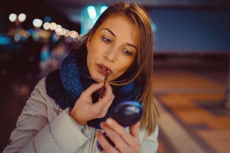 Beautiful woman applying lipstick at night