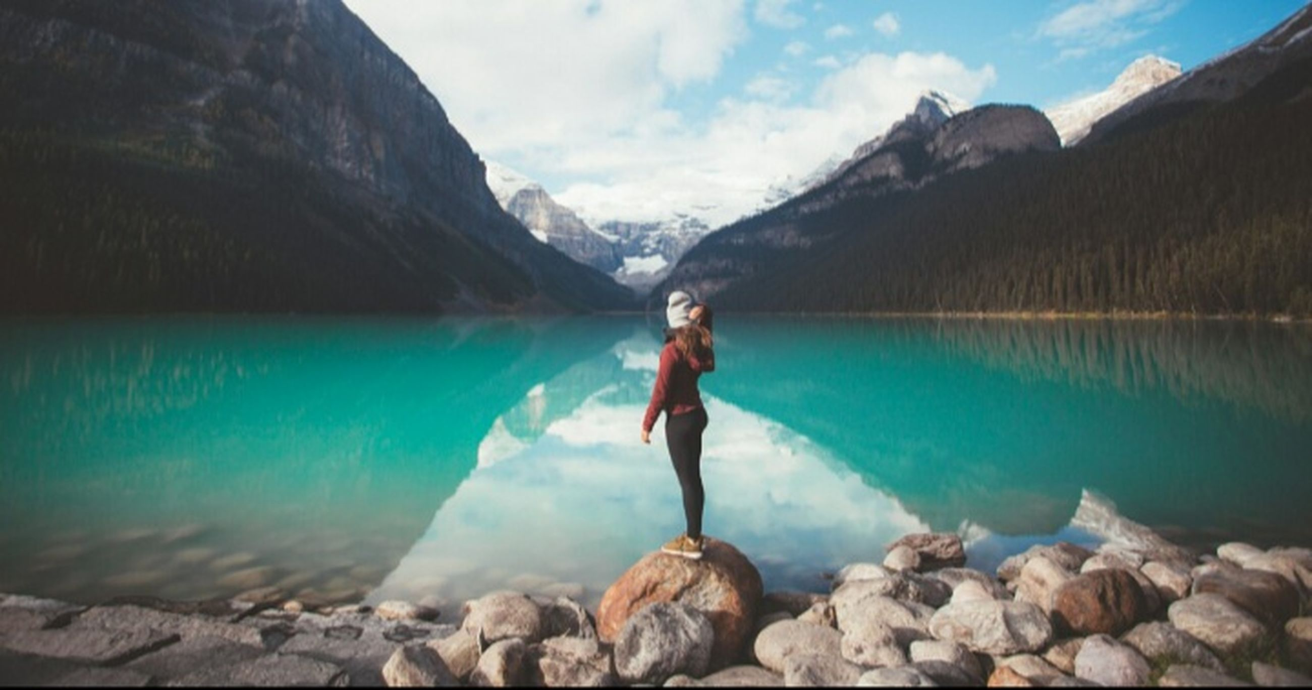 water, mountain, solid, rock, full length, one person, rock - object, beauty in nature, nature, scenics - nature, lake, holiday, vacations, sky, trip, day, cloud - sky, standing, mountain range, outdoors