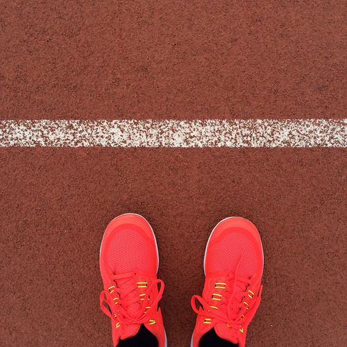 Low section of person wearing red shoes on running track