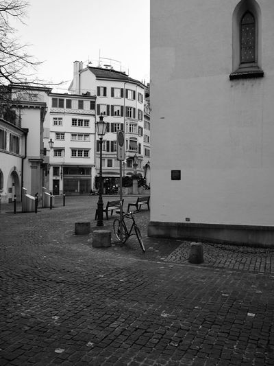 Bicycle parked on street against buildings in city
