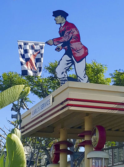 Checkered Racing Flag Communication Creativity Gas Pumps Gas Station Guy Information Sign Low Angle View Period Piece Racing Flag Red Jacket Vintage Signage