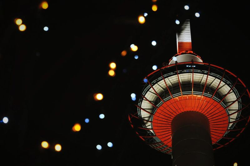 Low Angle View Of Illuminated Christmas Lights By Kyoto Tower At Night