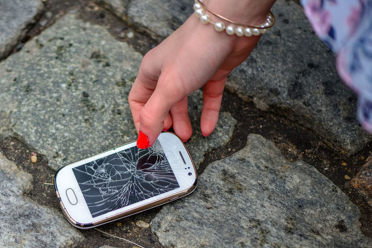 Person Picking Broken Smart Phone (Cracked Screen) of the Ground Crash Mobile Phone Screen Accident Broken Close-up Concept Destroy Device Digital Display Glass Ground Mobile Phone Smart Phone Stones Whie