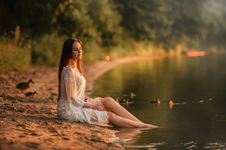 Woman sitting in water at sunset