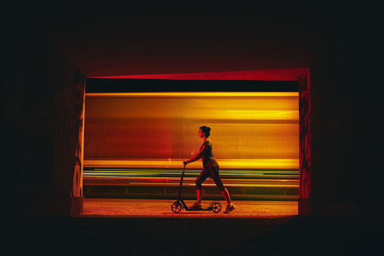 Side view of man cycling at night