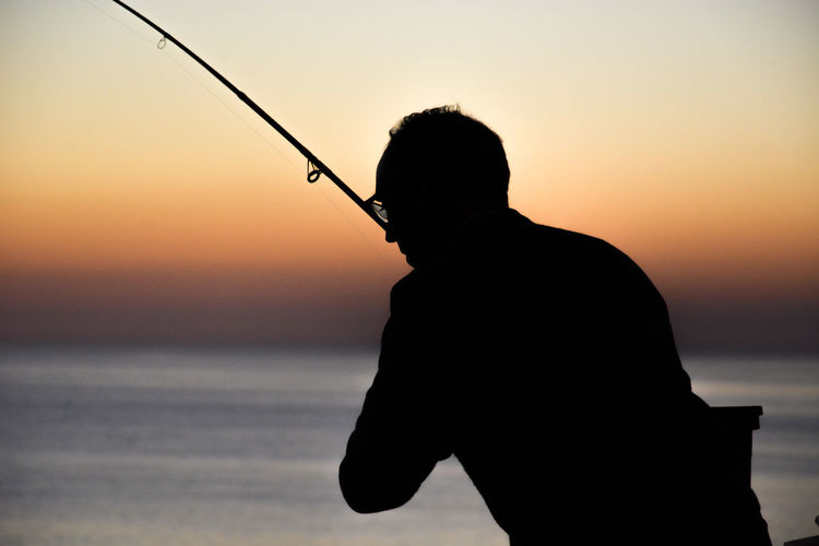 Silhouette man fishing at beach against sky during sunset