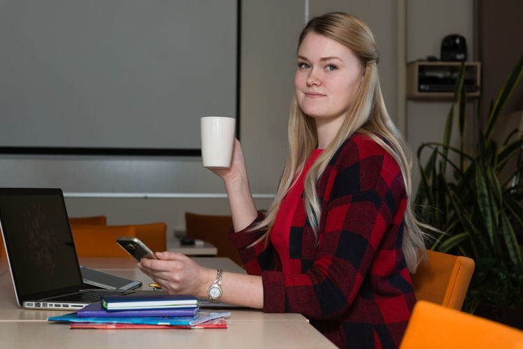Portrait Of Smiling Young Woman Holding Coffee And Phone By Laptop On Desk