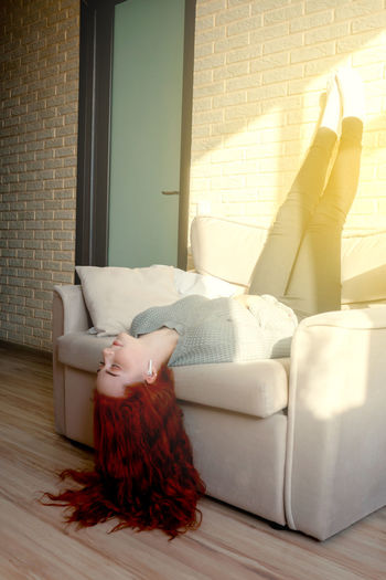 Midsection of woman relaxing on sofa at home